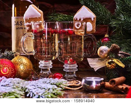 Close up Christmas still life with two mug hot drink. Warming mulled wine with cookie in form of house and Christmas ball in restaurant.
