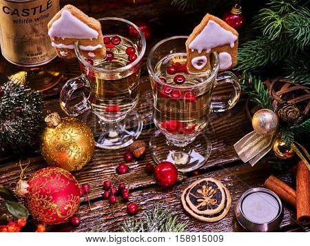 Top view Christmas still life with pair mug hot drink and wine bottle . Warming mulled wine with cookie in form of house and Christmas ball and candels.