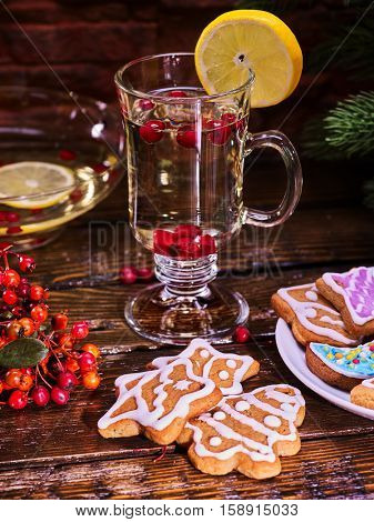 Christmas glass latte mug and Christmas multicolored cookies on plate with fir branches. Mag decoration lemon slice on wooden table in restaurant.