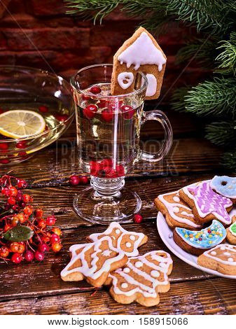 Christmas glass latte mug and Christmas multicolored cookies on plate with fir branches. Mag decoration cookie in form of house on wooden table in restaurant.
