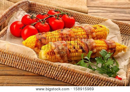 Grilled corncobs, tomatoes and parsley on wicker tray