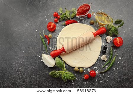 Raw pizza dough with ingredients on table