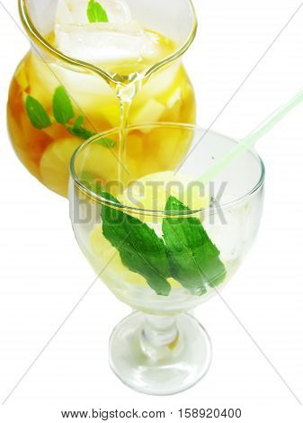 fruit juice cocktail punchpouring into glass with ice and fruit