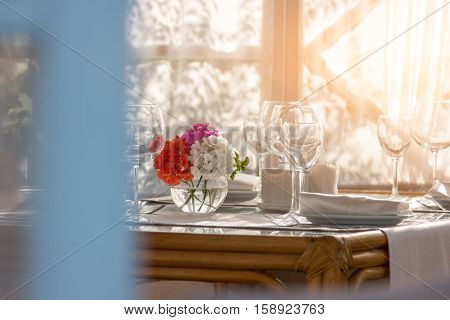 Flowers on the dining table. Plate and empty wineglasses. Invite your relatives for breakfast. Perfect order and cleanliness.