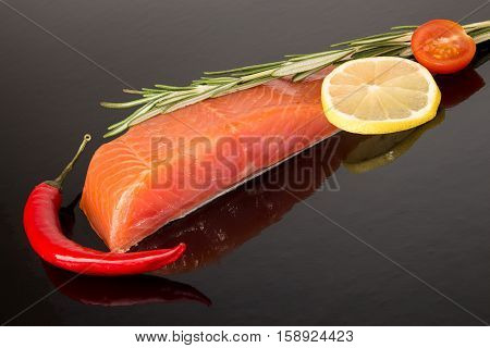 Salmon Fillet, Chili Peper, Lemon Slice And Tomato Over On Black Background.