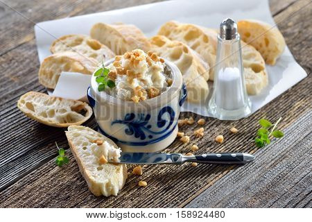 Hearty lard with greaves and onions in a rustic stoneware pot served with fresh corn bread on a rustic wooden table