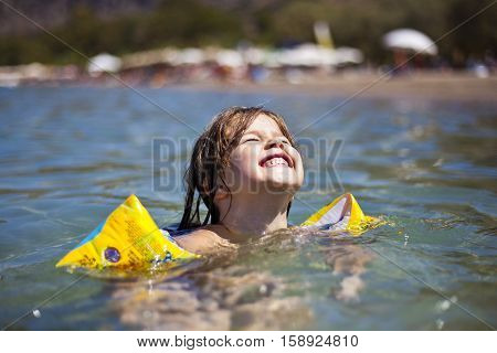 Portrait of happy child girl swimming in water