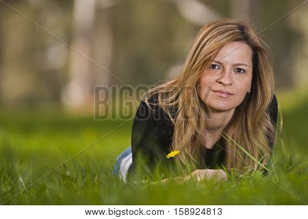 Young female sitting and smiling on grass
