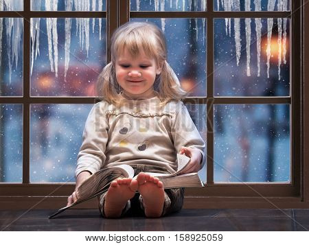 Little happy child reading a book. A large picture window. Outside the window snow falls winter. The house is warm the girl barefoot