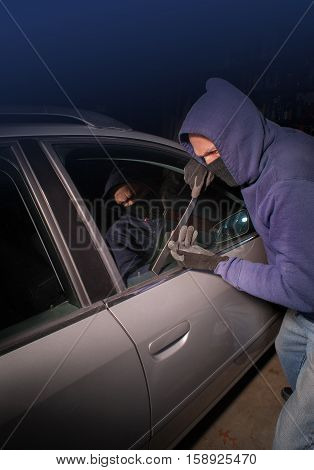 Car thief looking to open the lock on a vehicle