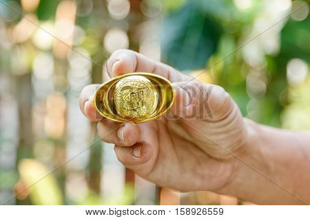 Hand giving gold ingot to someone for Chinese New Year celebration on red background