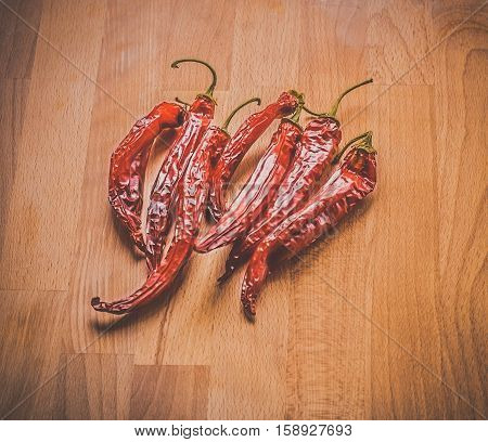 Spicy background with hot chilies over rusty wooden background. Top view. Row of red chillies on the light wooden background.