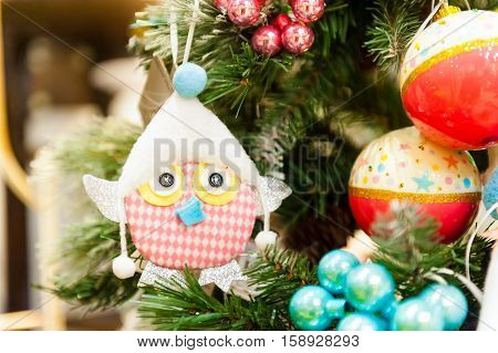 Christmas Fir Tree Toys hanging on branch Burning Candles, Boxes, Balls, Pine Cones, Walnuts, Branchesin the background other decorations and garlands.