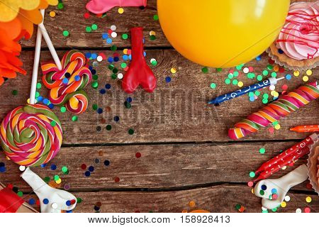 Birthday party objects on wooden background, top view