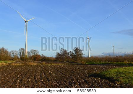 Row of three windturbines in a green surrounding.