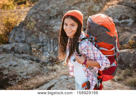 Tourist woman with backpack near the canyon. looking at camera. stands sideways. top view