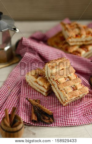 freshly baked slices of cake on a red-white napkin, a barrel of cinnamon coffee maker