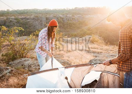 Tourists collect tent on mountain