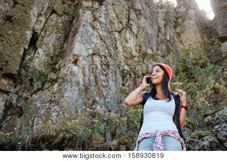 Traveling woman with back backpack talking on phone. from below image