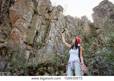 Young traveling woman with backpack and phone near the rock