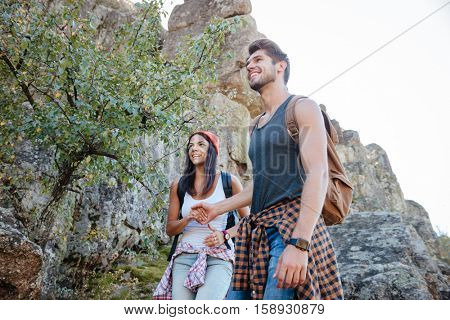 From below image of young happy couple walking on rock