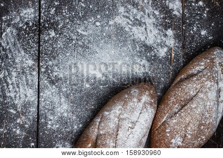 Two Black Bread With Flour On A Wooden Background. Advertising Bread. Leaning Flour. View From Above