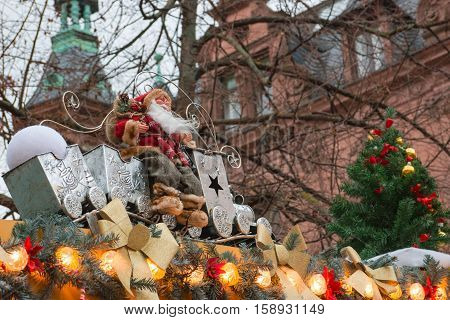 Christmas decoration: Santa Claus sitting on the roof decorated with garland and fir tree