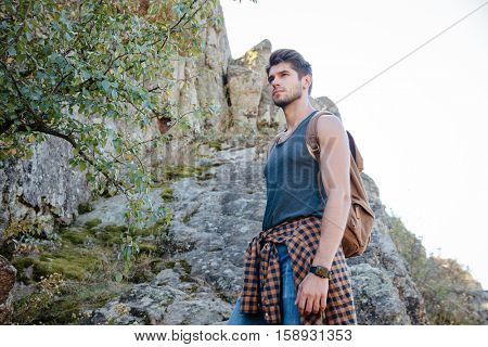 Young traveling man with backpack on rock. from below image