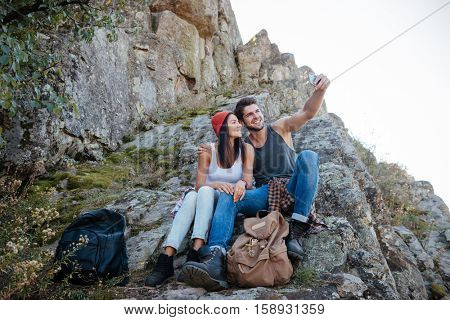 Young couple make selfie and sitting on rock. full length image