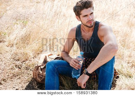 Portrait of a young male hiker with backpack resting and drinking water