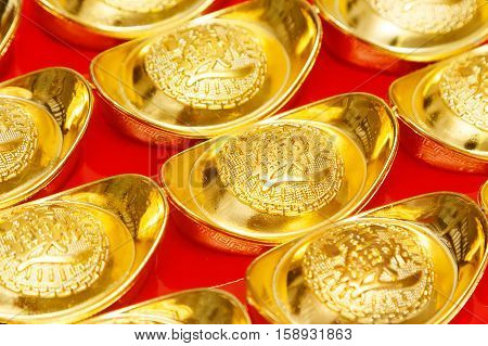 Gold ingot of China in the Chinese New Year festive on red Background.
