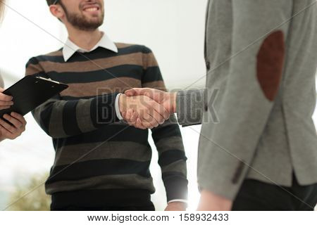 Two men shaking hands and looking at each other with smile