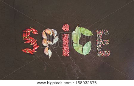Word Spice made from spicy background with assortment of different hot chilies, allspice, brazilian peppers, garlic and bay leaves over rusty black wooden background. Top view.
