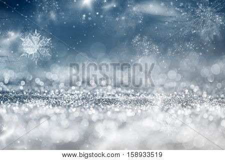 Magic blue holiday abstract glitter background with fireworks blinking stars and falling snowflakes. Blurred bokeh of Christmas lights.