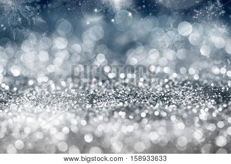 Magic blue holiday abstract glitter background with blinking stars and falling snowflakes. Blurred bokeh of Christmas lights.