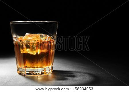 Glass of whisky on grey textured table closeup