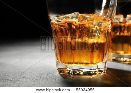 Glasses of whisky on grey textured table closeup