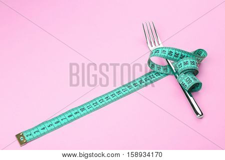 Measuring tape wrapped around fork lying on color surface. Diet concept