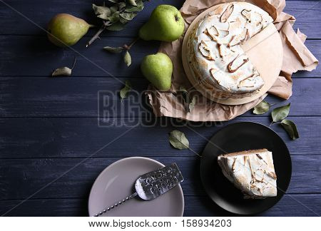Tasty cake with chocolate, nuts and pear topping on dark wooden background