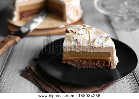 Slice of delicious cake with chocolate, nuts and pear topping on black plate