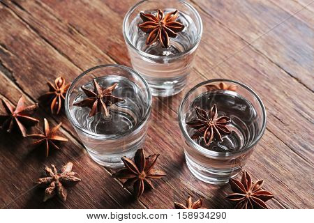 Vodka with anise on wooden background