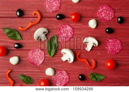 Pizza ingredients on wooden background