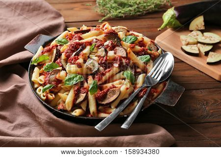 Pan with tasty macaroni, napkin, spoon and fork on wooden table