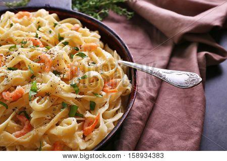 Pan with tasty alfredo pasta and napkin on dark table
