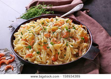 Pan with tasty alfredo pasta, napkin, prawns and herbs on dark table