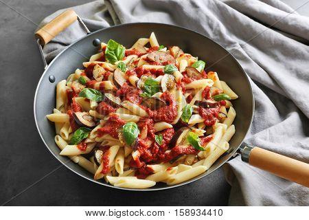 Pan with macaroni, basil, ketchup, eggplant slices and napkin on dark table