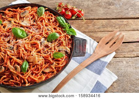 Pan with delicious pasta, cherry tomatoes, fork and napkin on wooden table