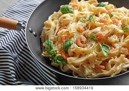Pan with tasty alfredo pasta and napkin on table