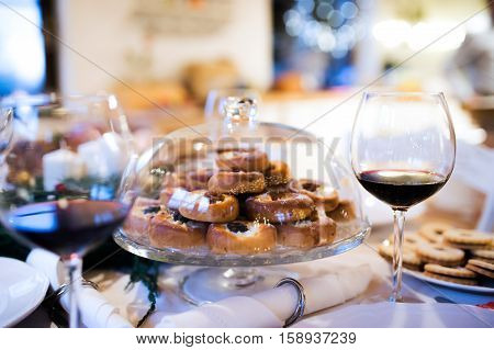 Christmas meal laid on a table in decorated dining room. Jelly cookies, pastry on cake tray and glass of red wine.