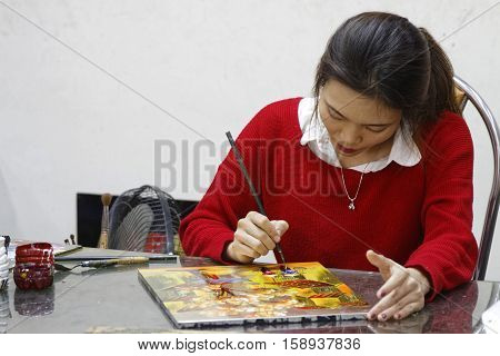 HANOI VIETNAM October 30 2016 : Unidentified artist paints in a workshop of lacquer of Hanoi. Lacquerware are objects decoratively covered with lacquer mostly from East Asian cultures.